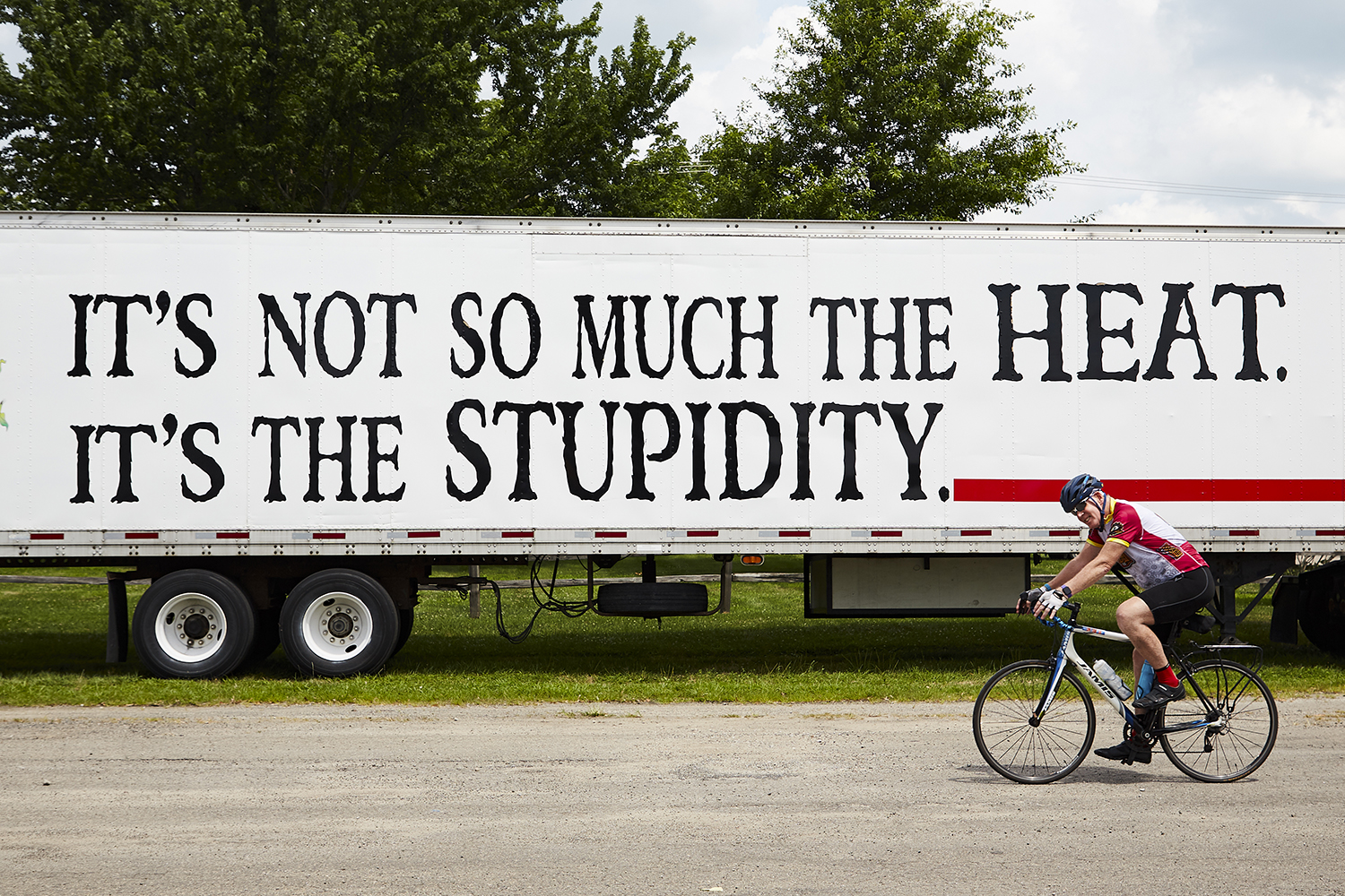 A cyclist rides past a support truck as the Register's Annual Great Bicycle Ride Across Iowa (RAGBRAI) pulls into Fairfield, IA as part of  RAGBRAI XLVII on Thursday, July 25, 2019.
