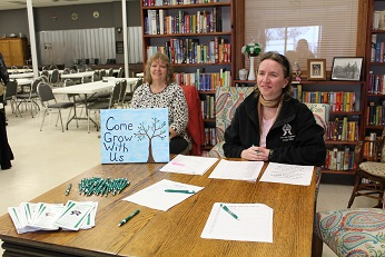 "Women sitting at a table with a sign that says, ""Come grow with us"""