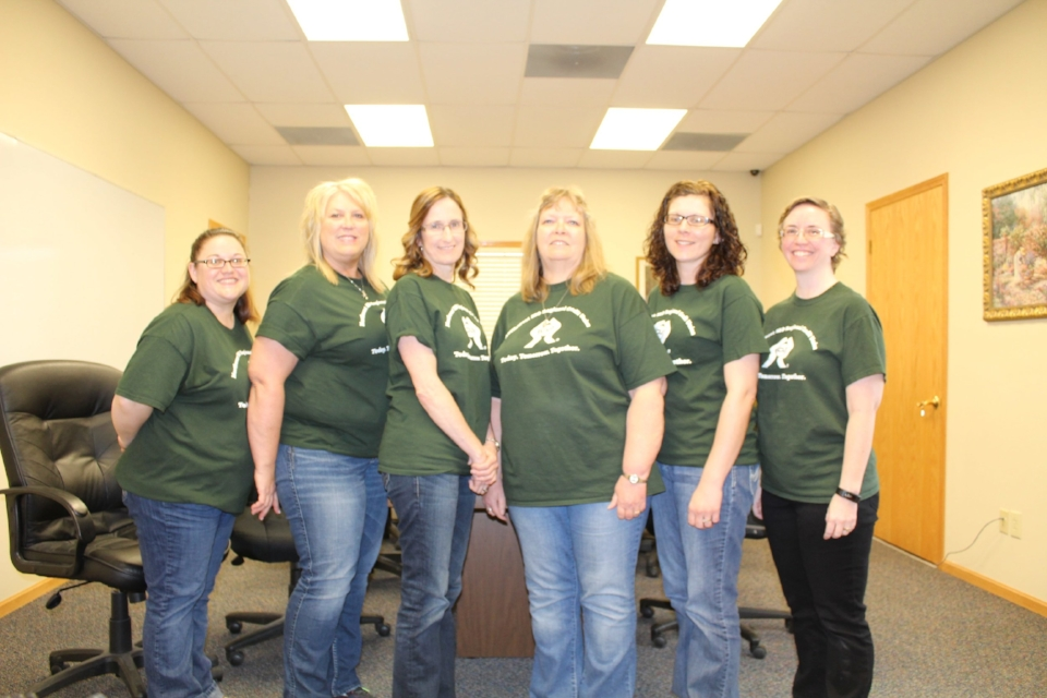 Group of 6 women wearing a green shirt and jeans, all staff of NW MS CU as of April 2016.