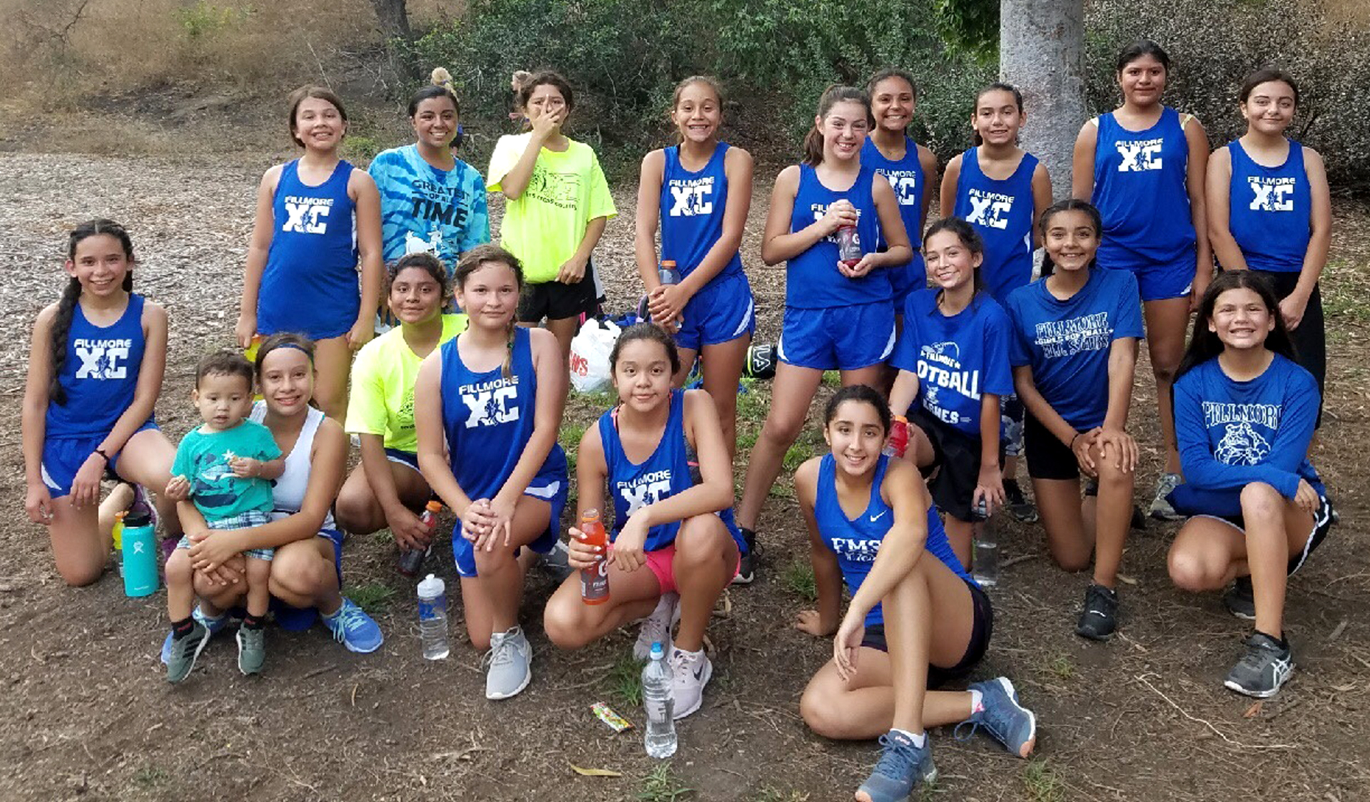 Female members of Fillmore Middle School's Cross Country Team, coached by Priscilla Montero, smile before getting ready to run.