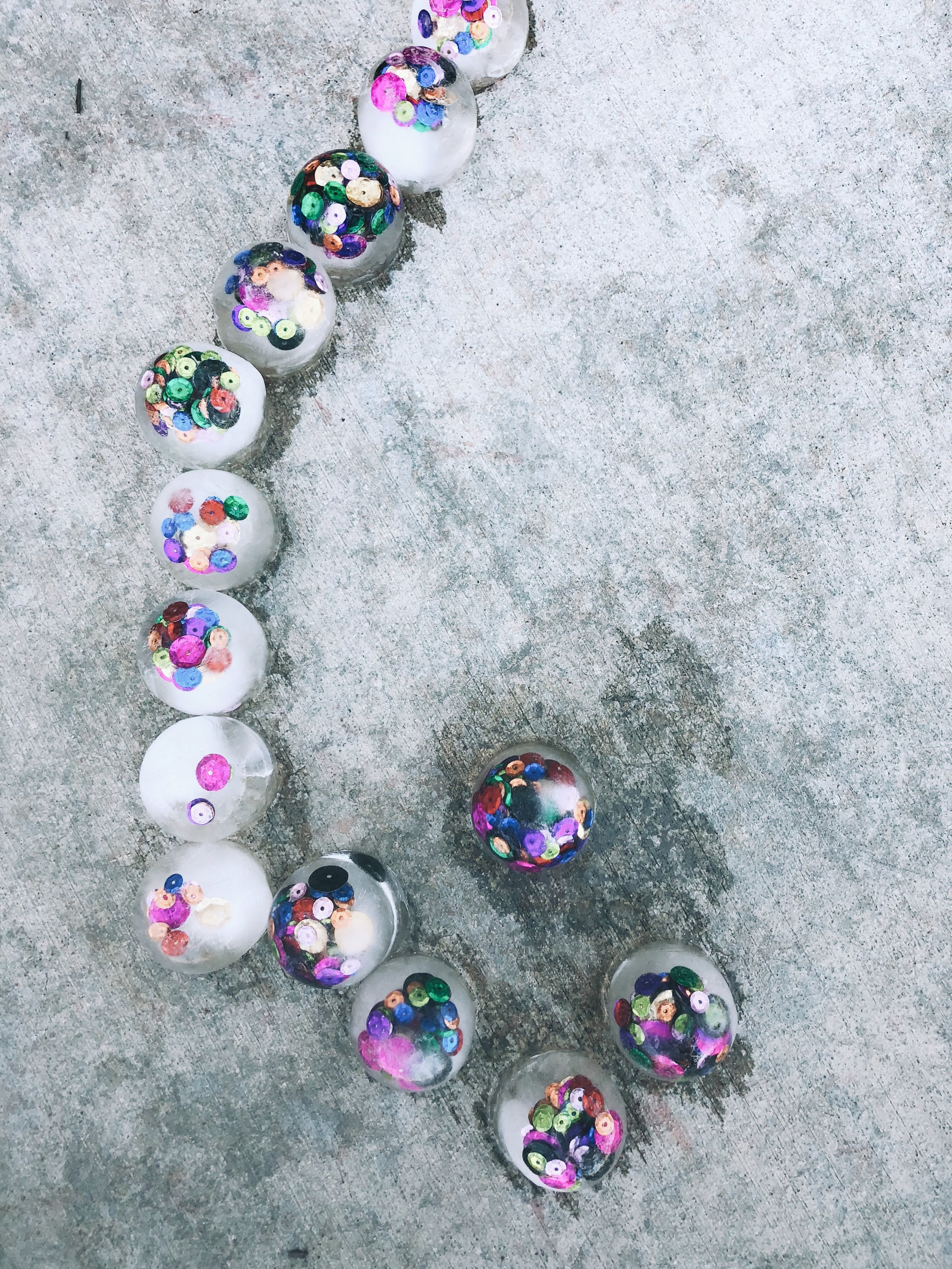 an adorable neighborhood boy (probably only 18 months old) walked by while we were playing with our confetti ice, lined them up like this and then walked away. It was adorable!