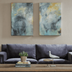 Paired canvas art over blue sofa