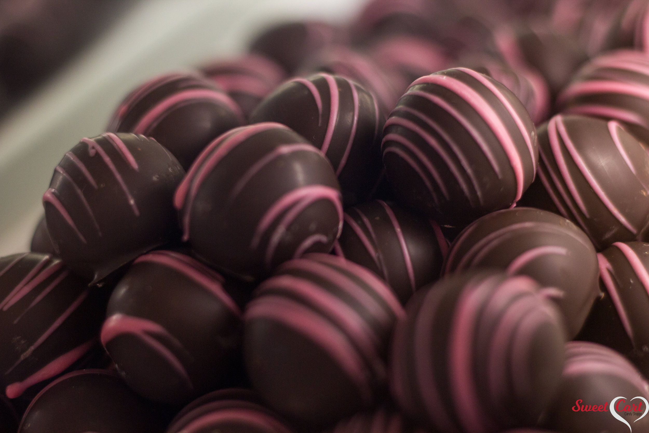 Raspberry Truffles   Rich Dark Chocolate inside & out. Accented with a Raspberry Drizzle making for a delicious combination of flavors!