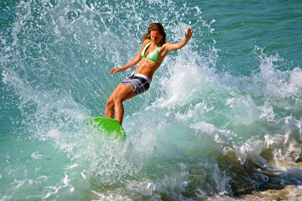 Erin skimming big surf. (photo courtesy of Chris Beletsis)