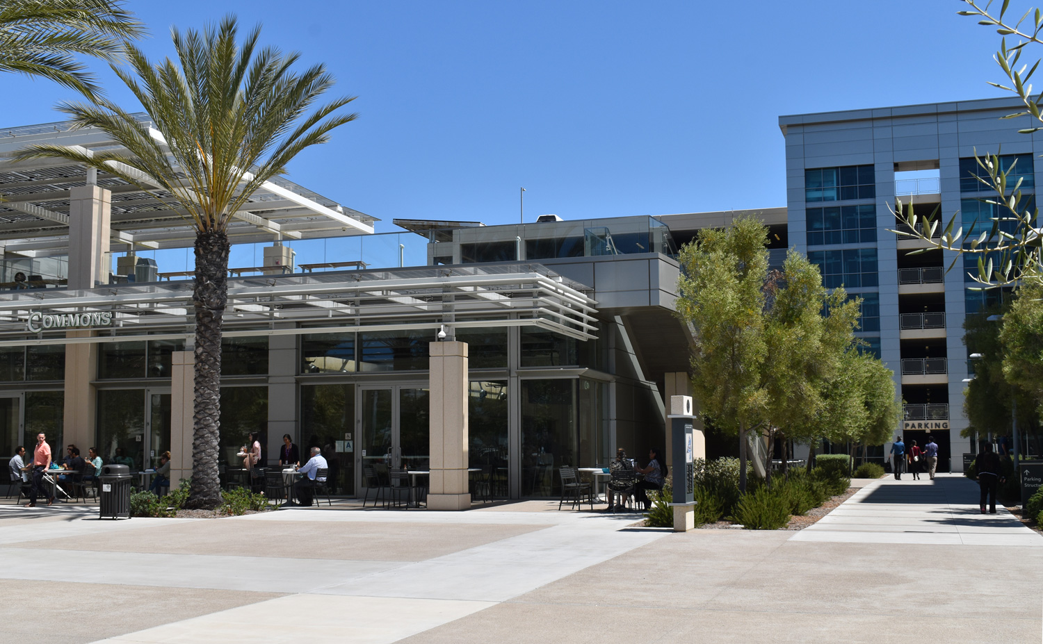 The meetings will be held in the Campus Center Chambers, within the building seen to the left. The parking structure is seen on the right.