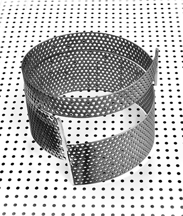 Round bangle with perforation. Sandblasted. Photographed on the paper used by architect to make paper mock-ups.