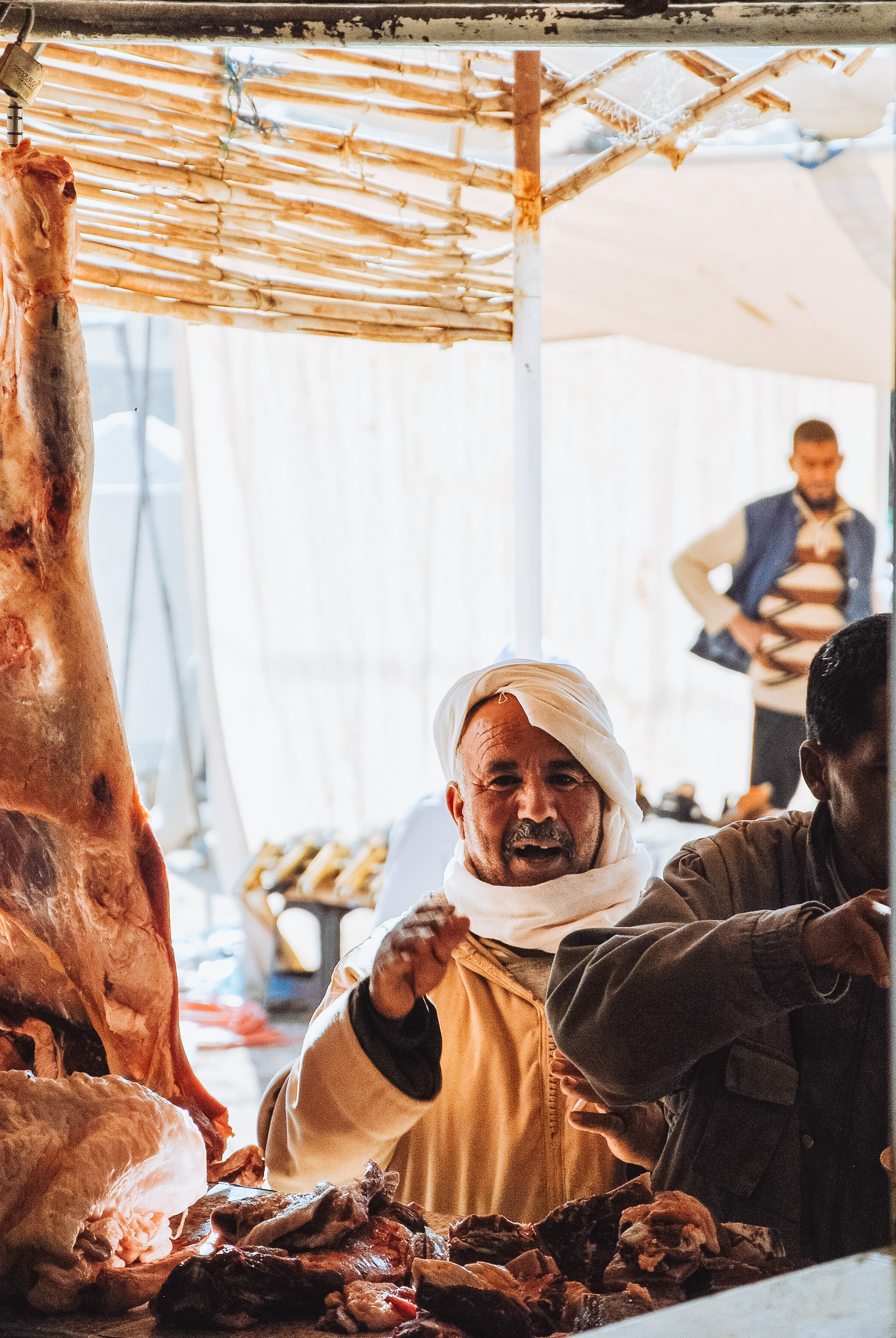 Meat hanging in shade of a shop