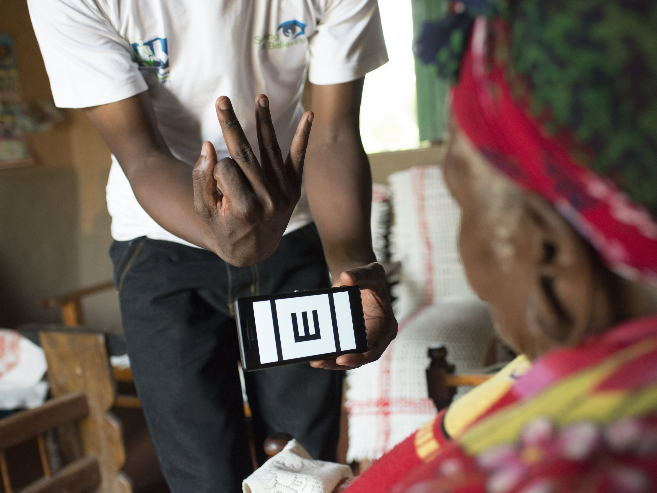 A health worker shows a lady how the Peek vision check app works in her home in Kenya
