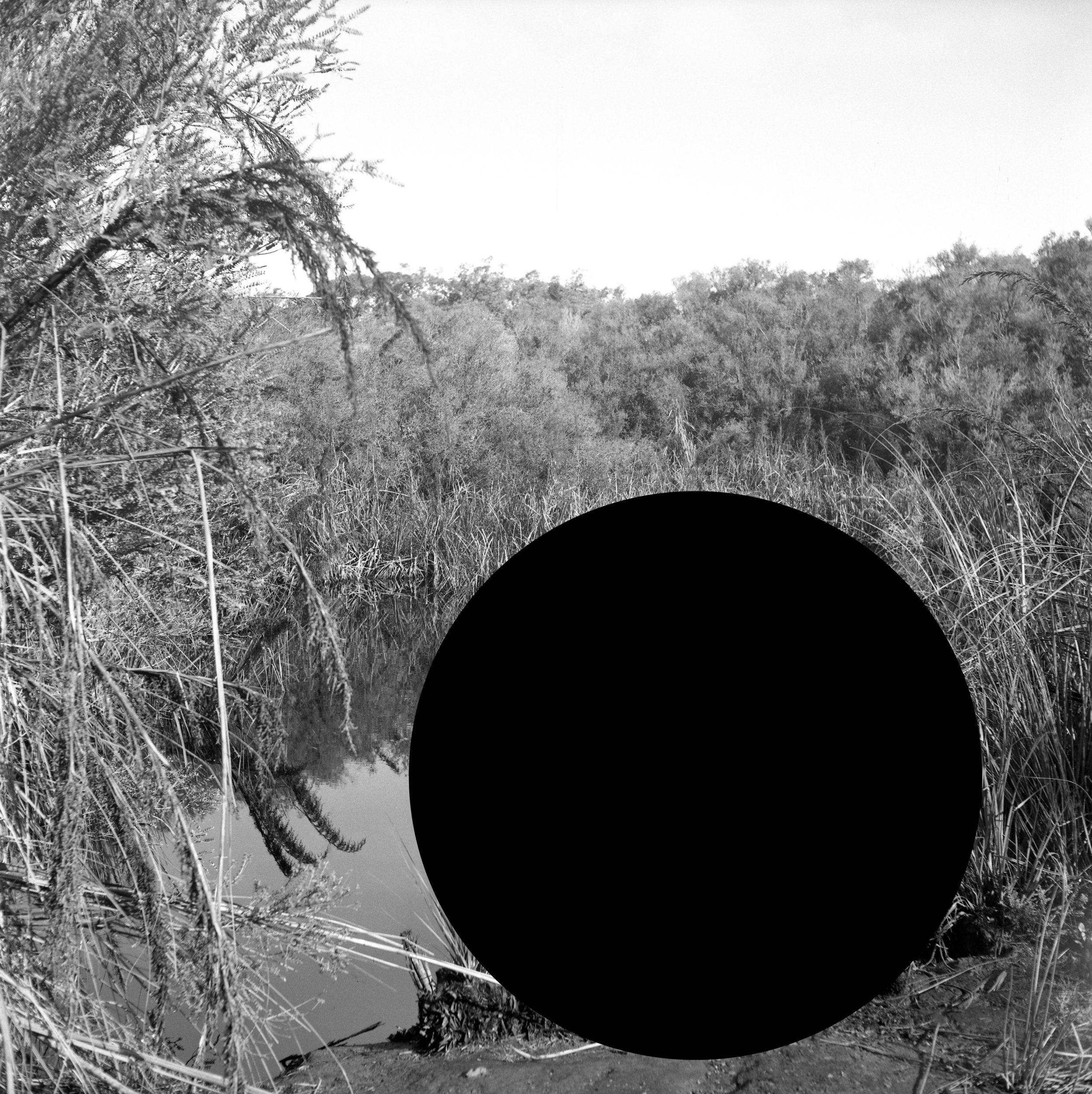"James Tylor ,  James Tylor, ""(Erased Scenes) From an Untouched Landscape #2"", 2014.  Narrawong State Forest, Gunditjmara nation, Victoria. Inkjet print on hahnemuhle paper with hole removed to a black velvet void, 60 x 60cm (framed) Courtesy the artist and Vivien Anderson Gallery."