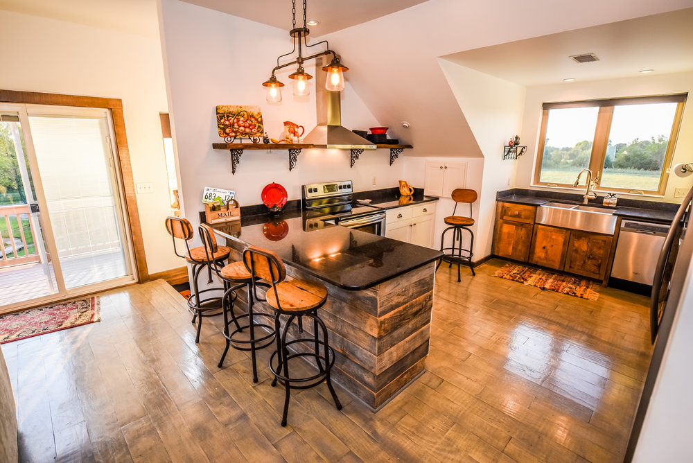 Charming rustic kitchen with window overlooking the farm and sunset fields.