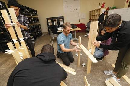 Montclair State University's Making and Innovating for X (MIX) Lab co-director Iain Kerr, center, works with Innovation Class students on an experimental connector exercise with 3-D-generated forms. - (AARON HOUSTON)