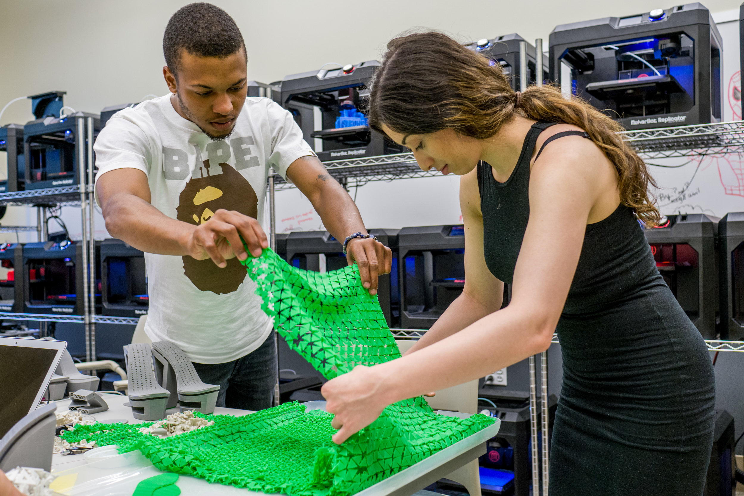 Altarik & Natalie assemble the sheets of 3D Printed pieces. (Photo by Mike Peters)