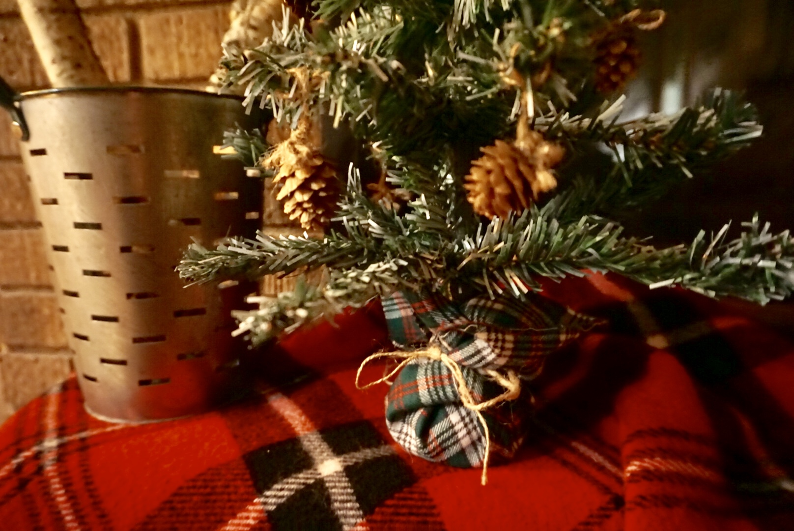 Plaid fabric and twine make a cute base for a DIY dollar store Christmas tree makeover.