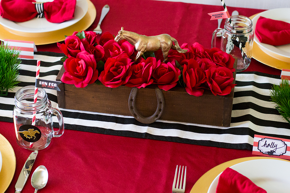 Kentucky Derby centerpiece decoration made of faux roses and toy horses spray painted gold.