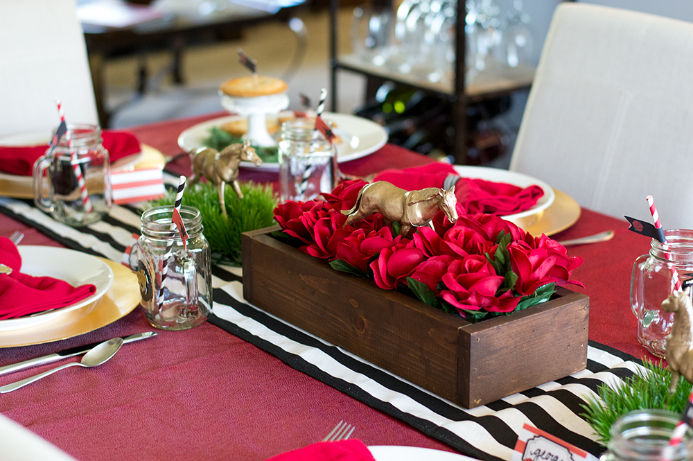 Kentucky Derby centerpiece box made with faux roses and gold spray painted toy horses.