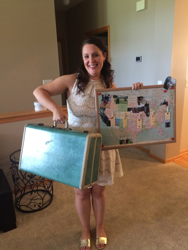 Bride at her travel themed bridal shower with vintage suitcase and map of places the couple has been.