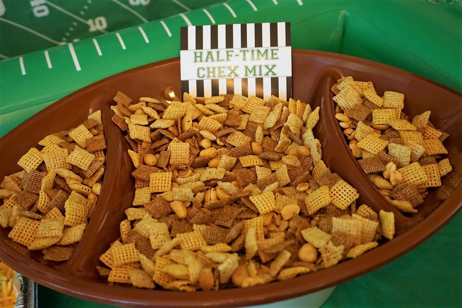 Chex mix in a football shaped bowl for football snacks.