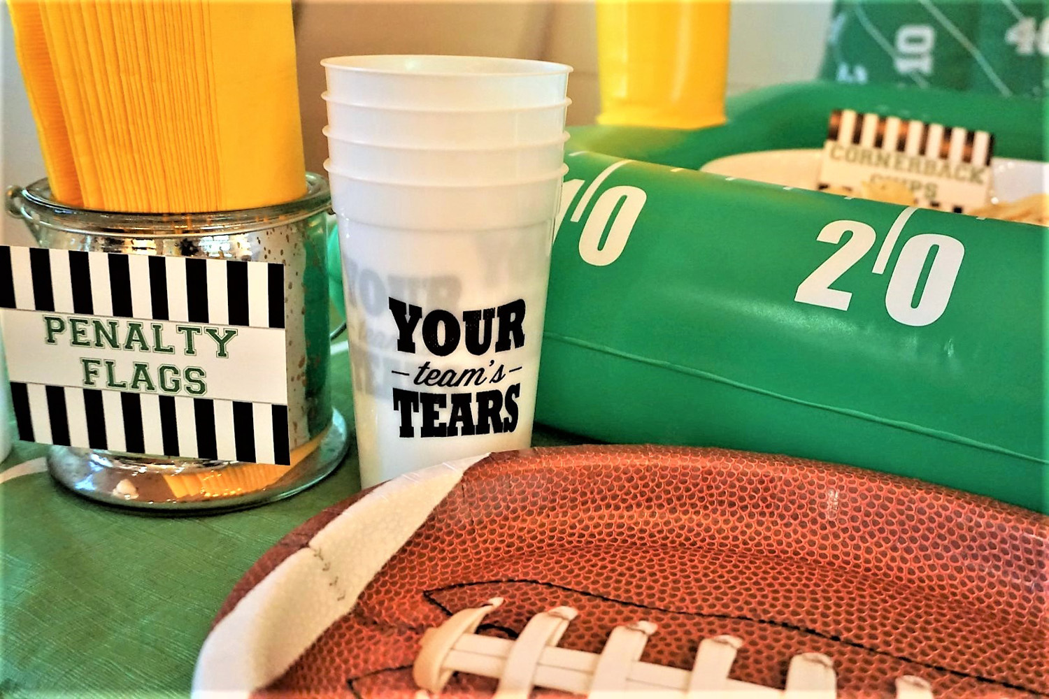 Football plates, yellow penalty flag napkins, and plastic beer cups