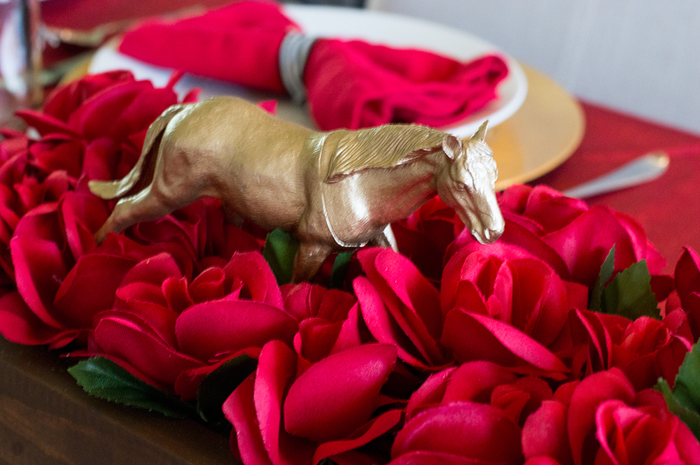 Gold spray painted toy horse and roses make a perfect Kentucky Derby party centerpiece.