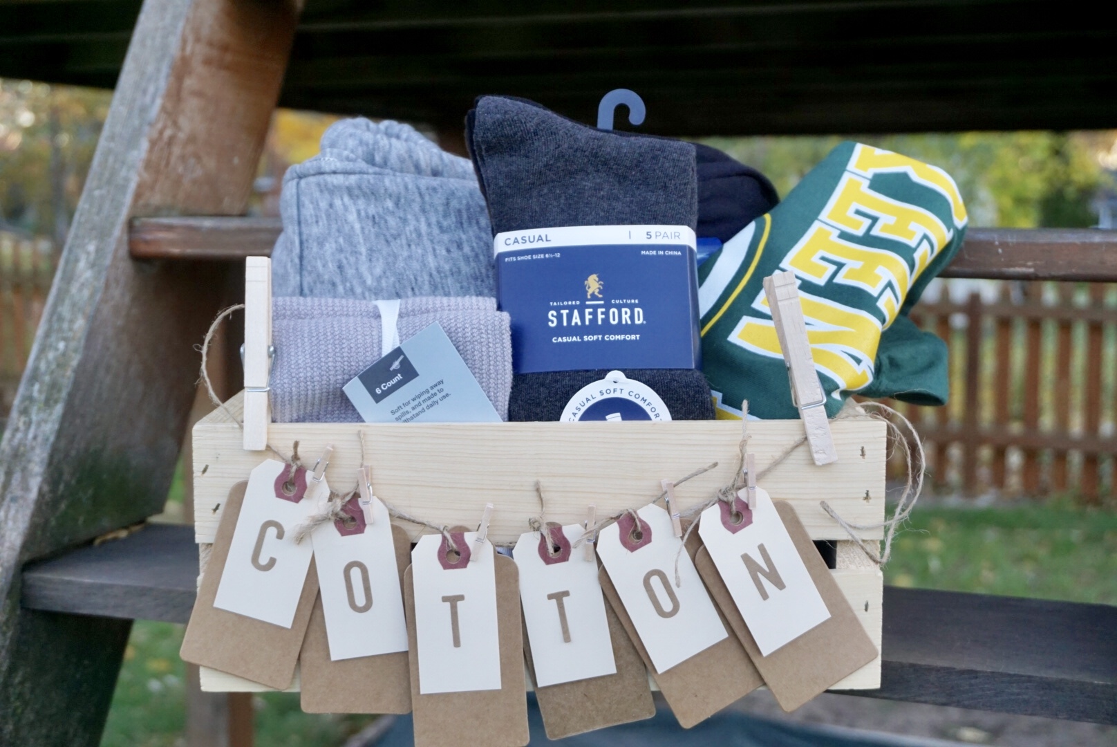 DIY Cotton 2nd Anniversary Gift Basket for your husband. Full of cotton goodies like t-shirts, socks, sweatshirt, dish cloths, and more! Click here to learn how to re-create for your own special day. #anniversarygift #secondyearofmarriage #diygiftbasket #giftbasketideas