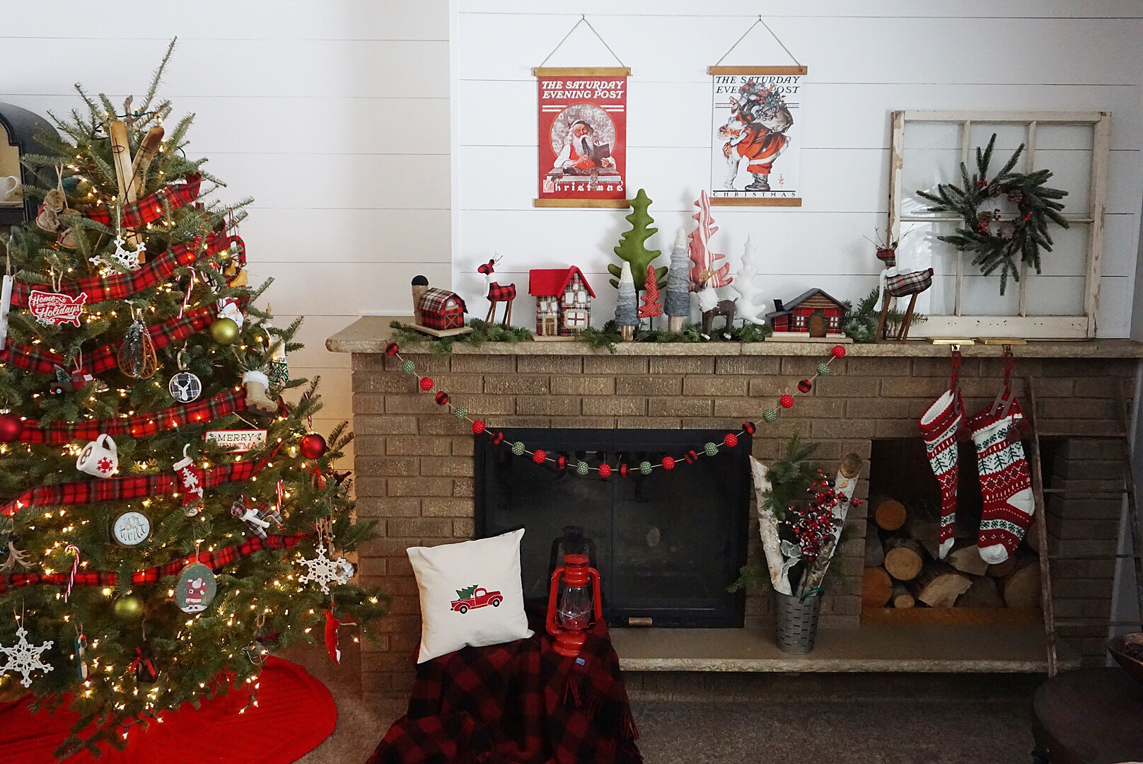 A vintage themed Christmas mantel with plaid houses, plaid pom garland, and vintage posters.