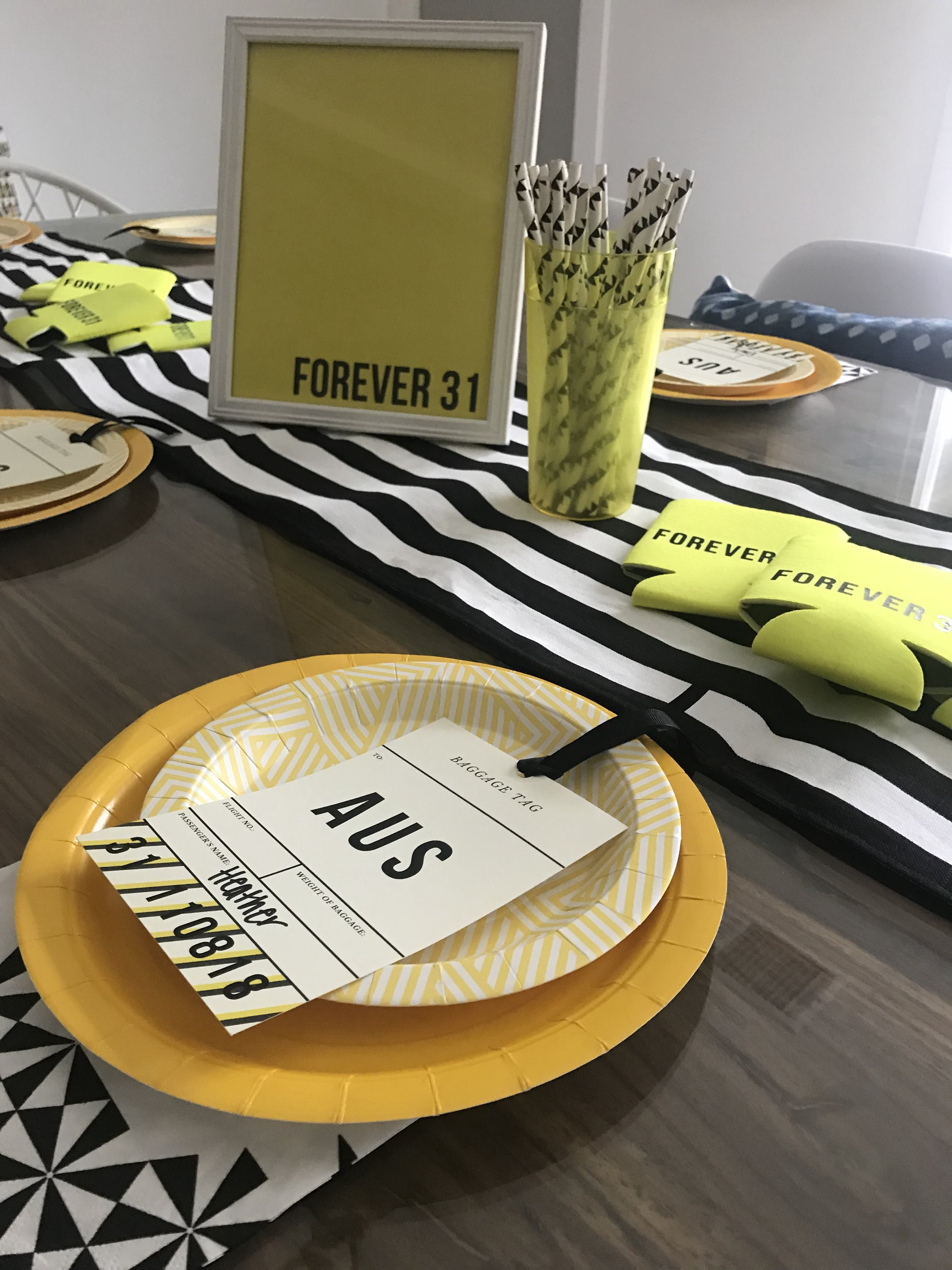 Yellow solid paper plates and geometric yellow plates along with black geometric paper straws and napkins.