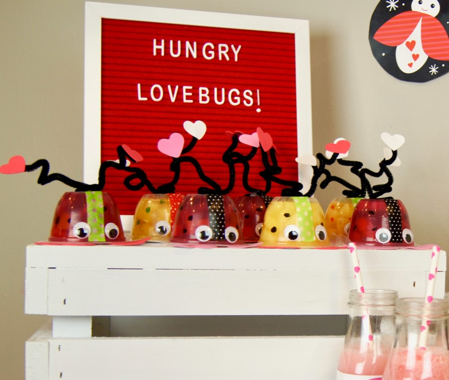 DIY love bug Valentine snacks made with fruit cups, washi tape, foam hearts, pipe cleaners, googly eyes, and markers.
