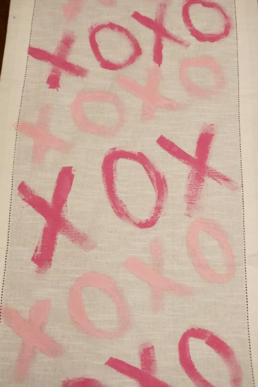 XOXO painted in pink paint on a table runner.