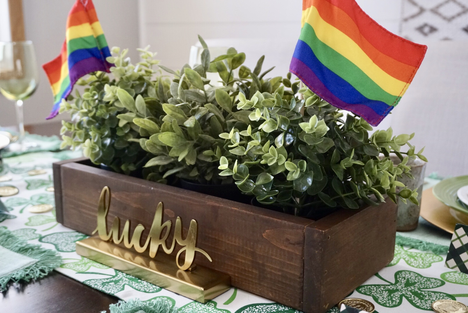 Lucky St. Patrick's Day Centerpiece with greenery, rainbow flags, and gold signage.