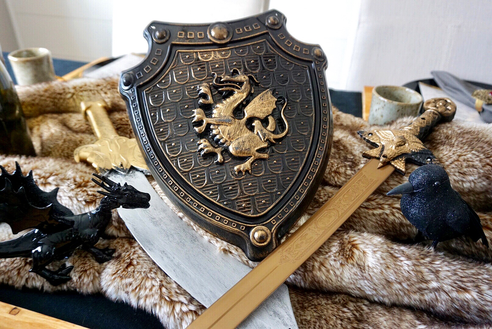 Toy swords and shield, a spray painted dragon, and a crow make an easy Game of Thrones themed centerpiece.