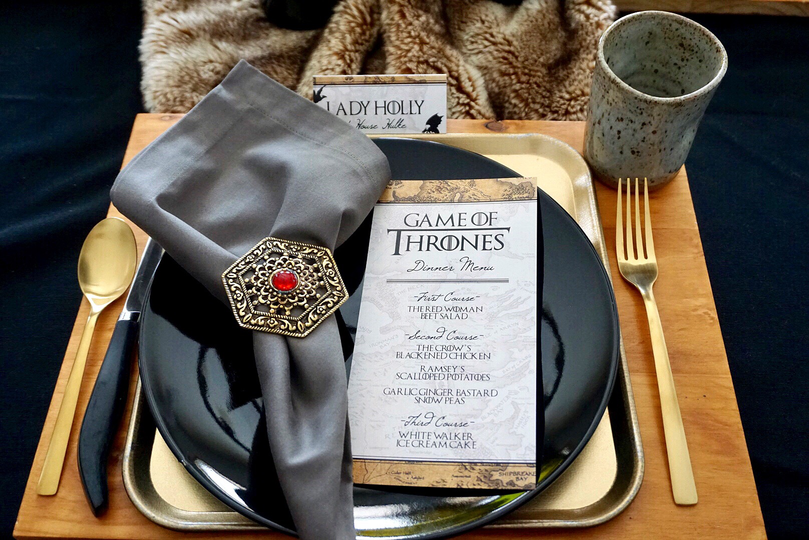 Wood chargers, gold trays, and black plates make the perfect layers for a Game of Thrones themed place setting.