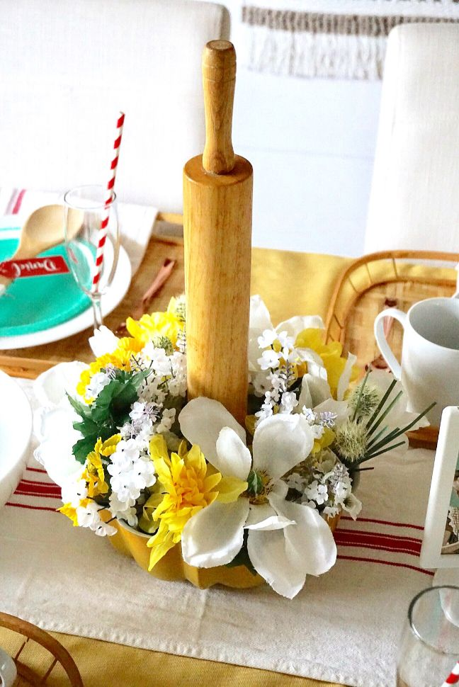 A bundt pan filled with dollar store floral and a vintage rolling pin is perfect for a DIY brunch centerpiece.