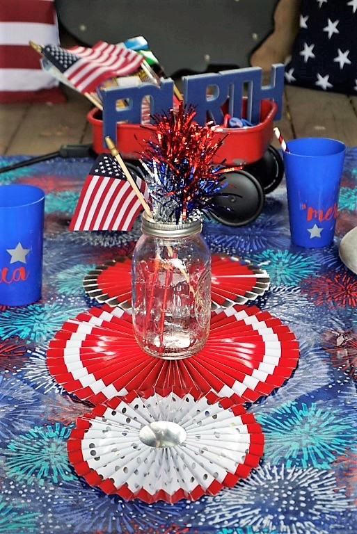An easy DIY 4th of July centerpiece made with metallic decor, an American flag, and a mason jar. Throw in some paper fans and you're done!