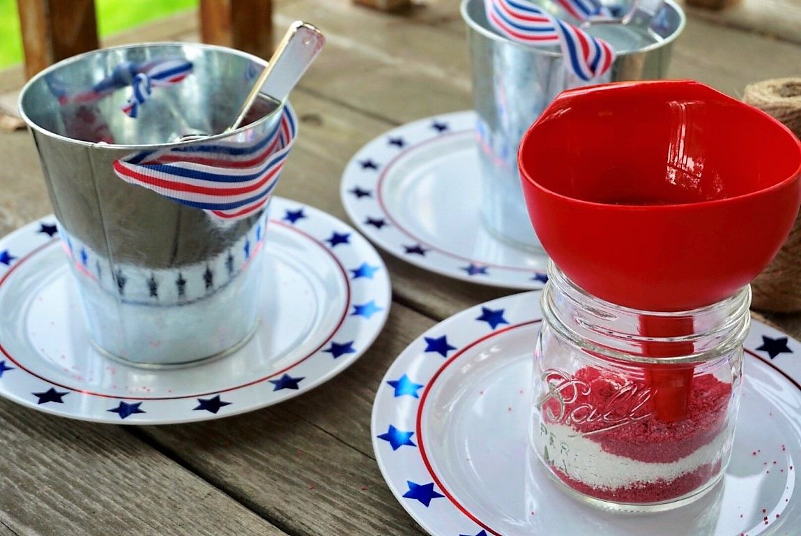 Use a funnel to put sand into Ball mason jars to make DIY sand art with kids at your 4th of July BBQ.
