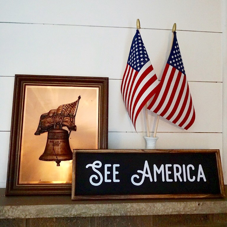 Copper liberty bell, American flags, and See America sign.