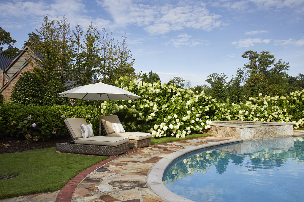 Two lawn chairs on the grass next to beautiful flower bushes & pool.