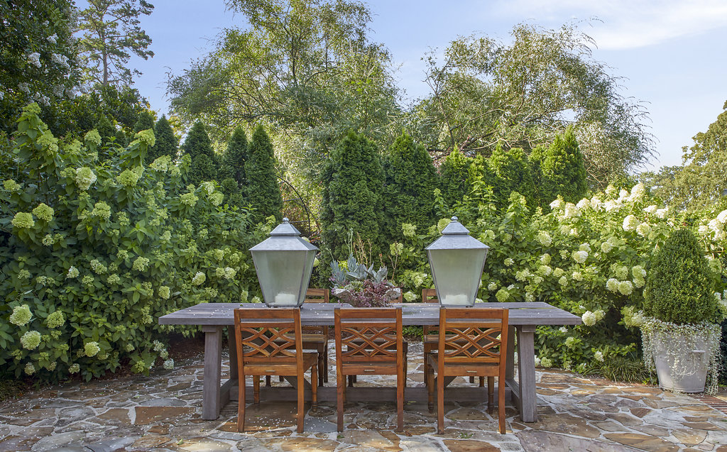 Flower bushes and trees surround an outside dining area.