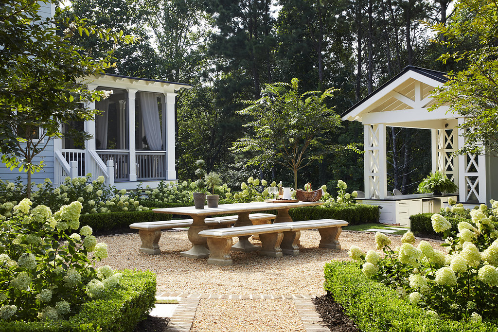 Hydrangea bushes line a walkway to an outdoor entertainment area.