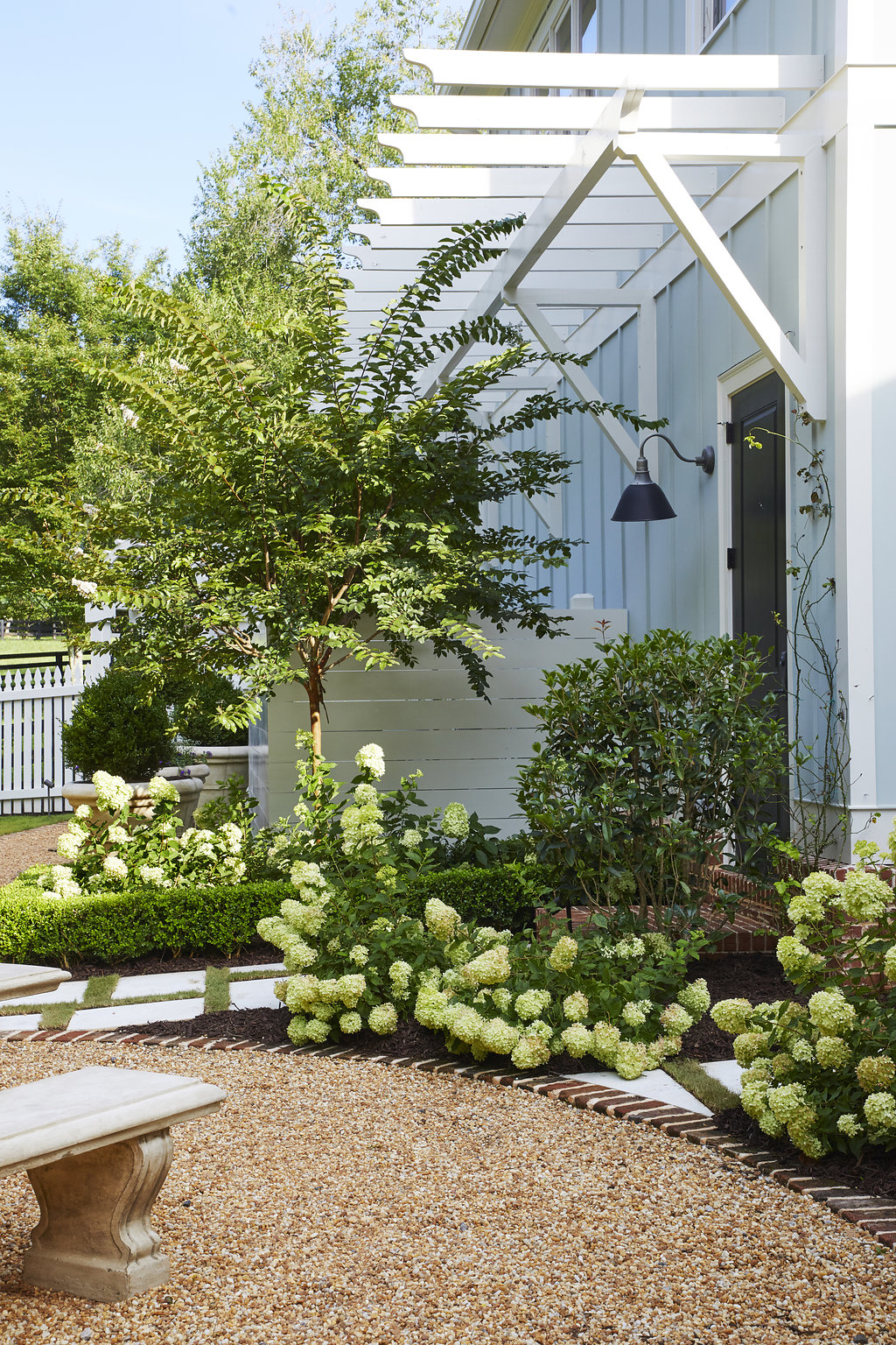 Hydrangea bushes and trees next to the entrance of the home.