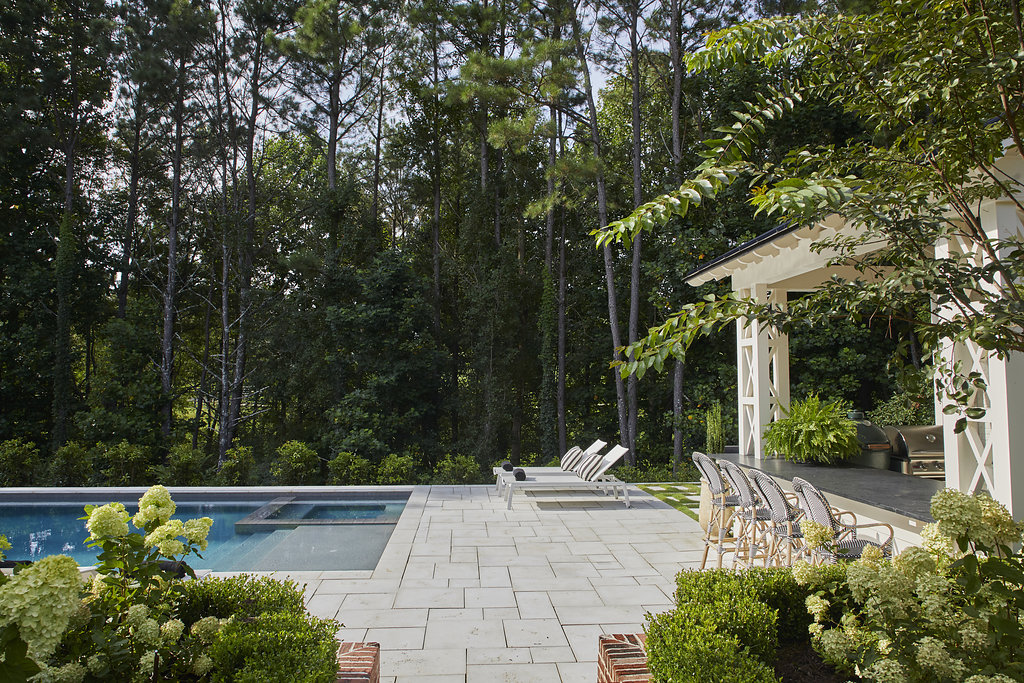 Shrubbery and trees surround a custom built pool and lawn chairs.