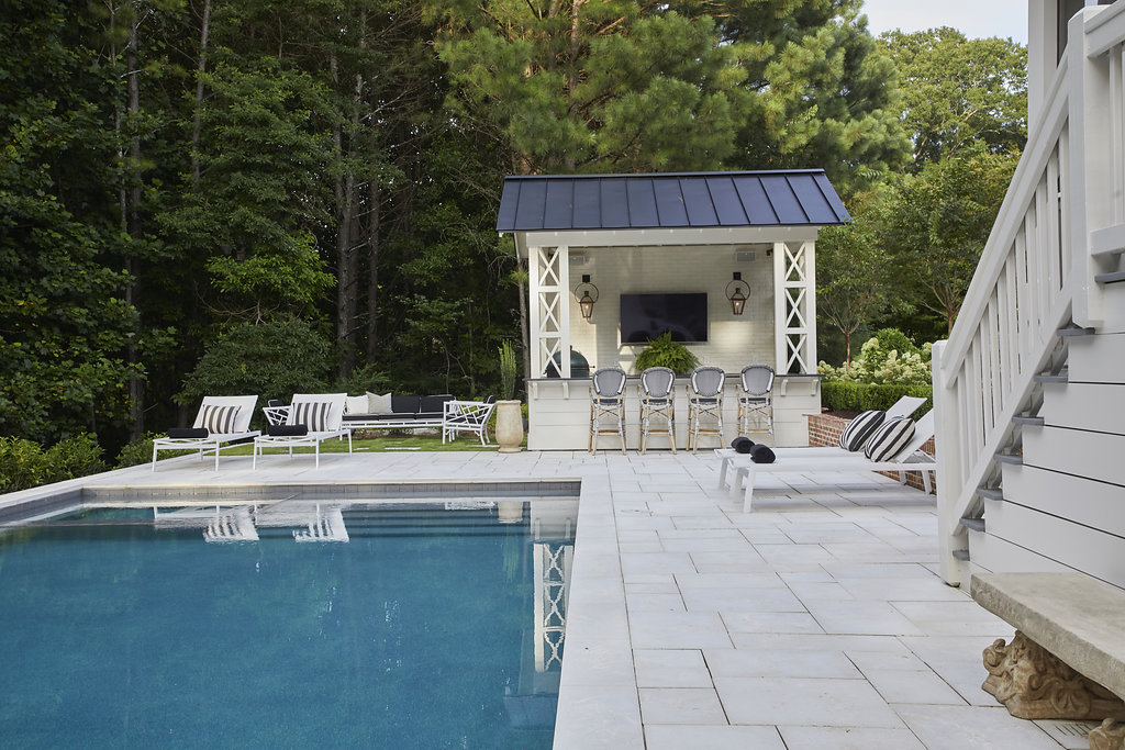 Another view of the pool leading into a covered entertainment area.