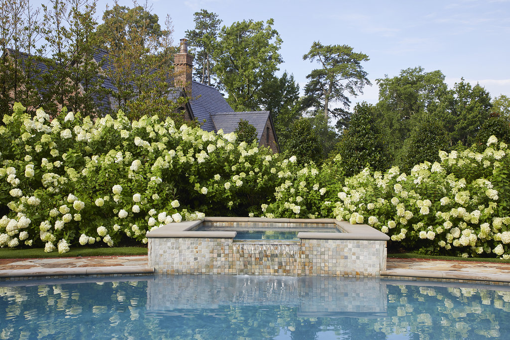 Flower bushes surround the jacuzzi and poolside.
