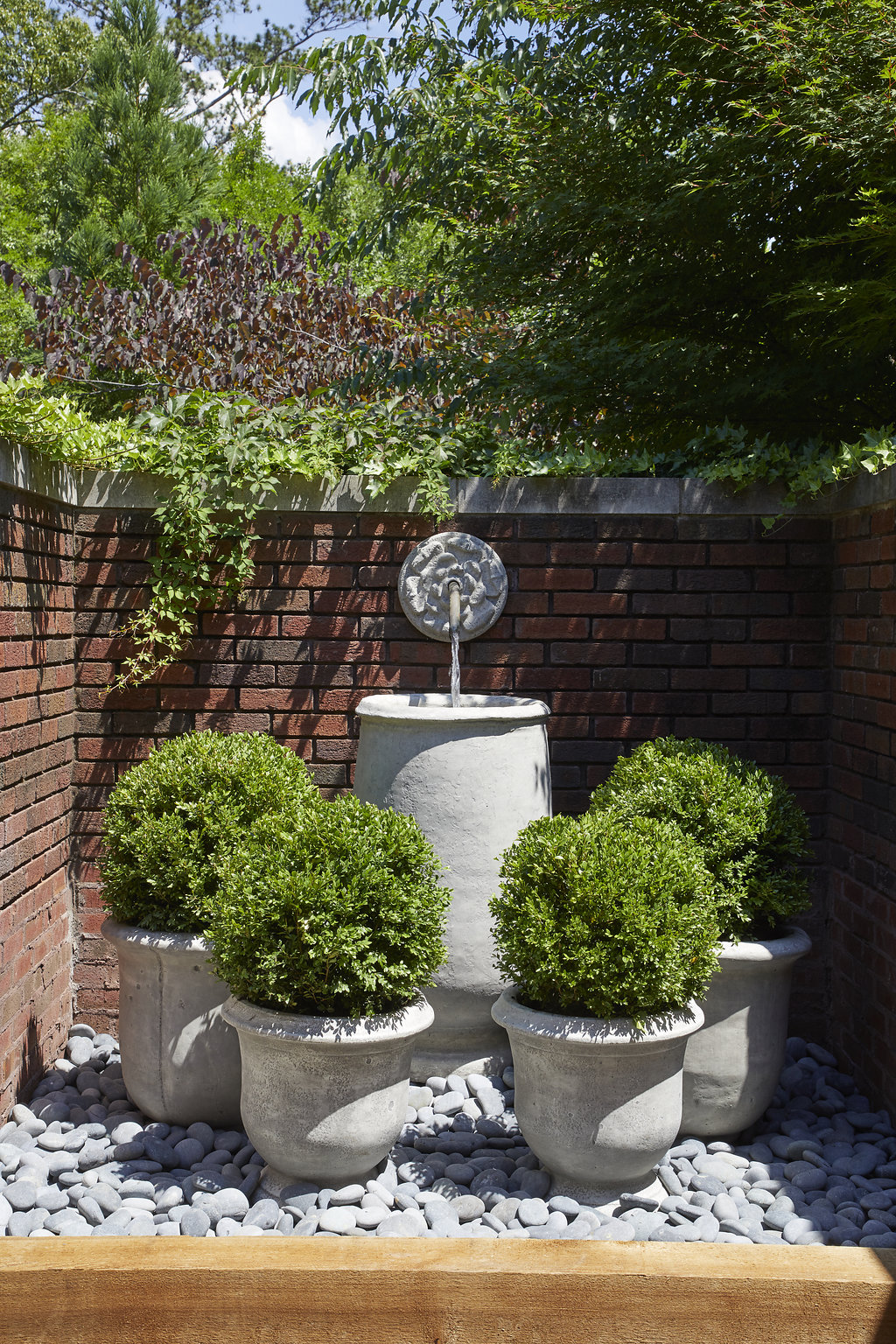 Custom built fountain surrounded by shrubs planted inside of custom built planters.