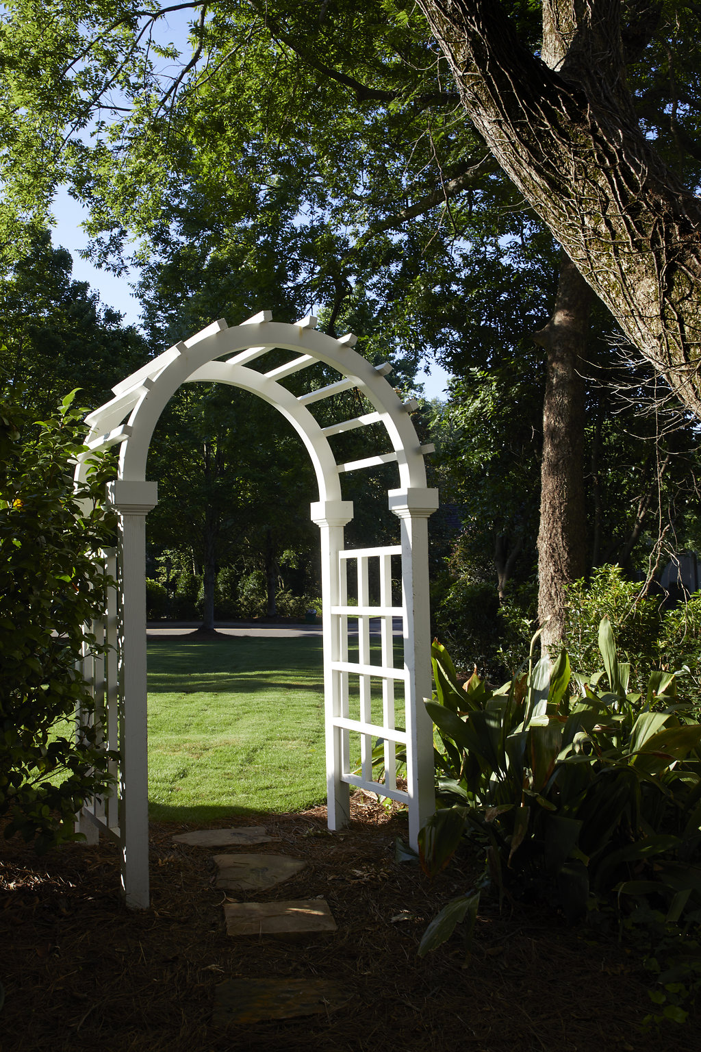 Archway surrounded by greenery and trees.