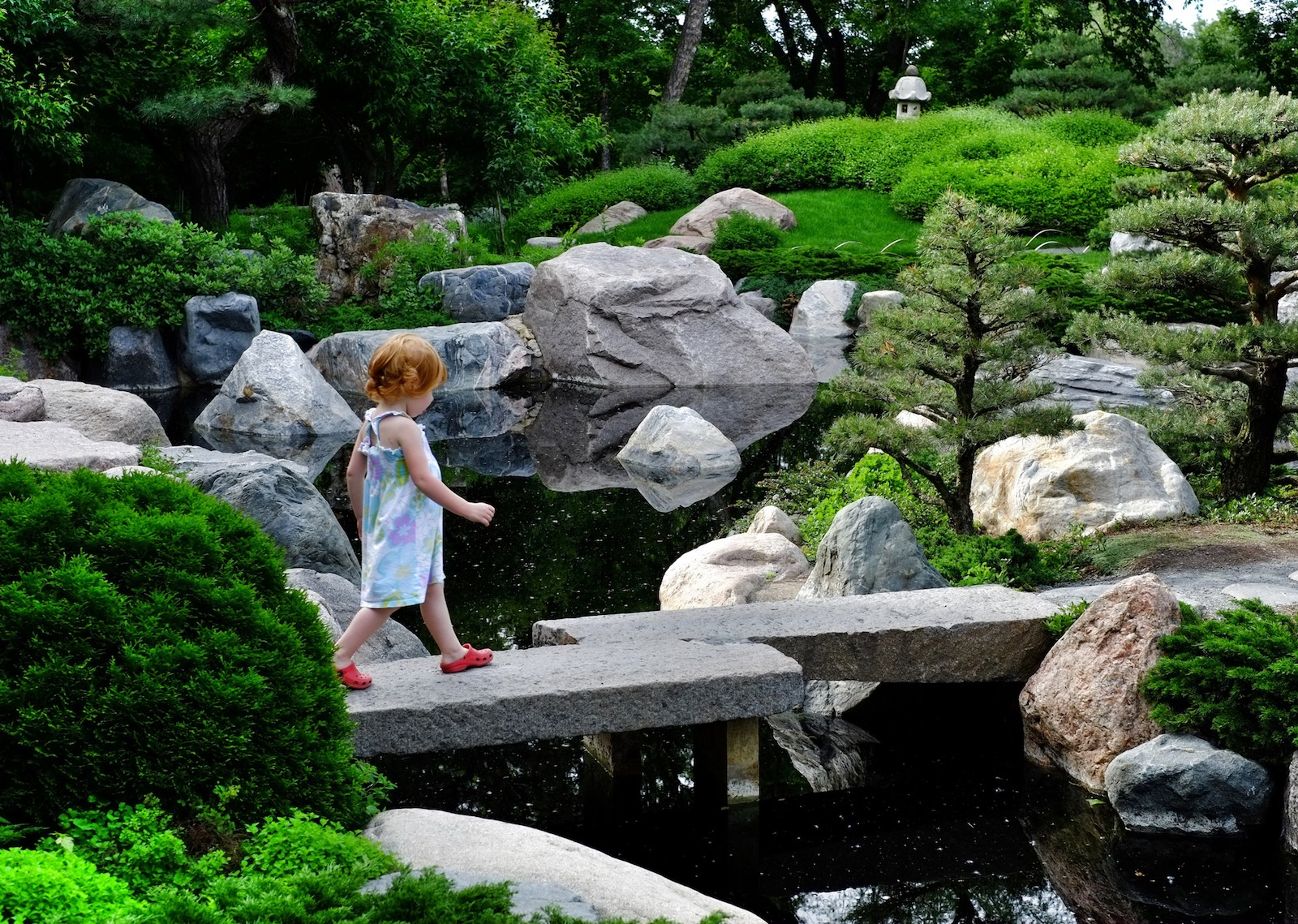 small young girl with red hair walking on stone bridge in japanese garden