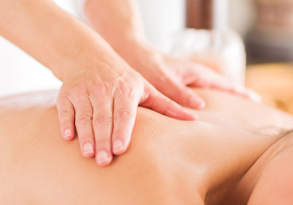 hands massaging someone's back