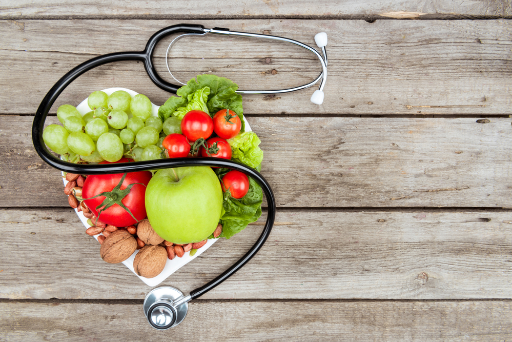 fruits and vegetables with stethoscope in heart shape on wood planks