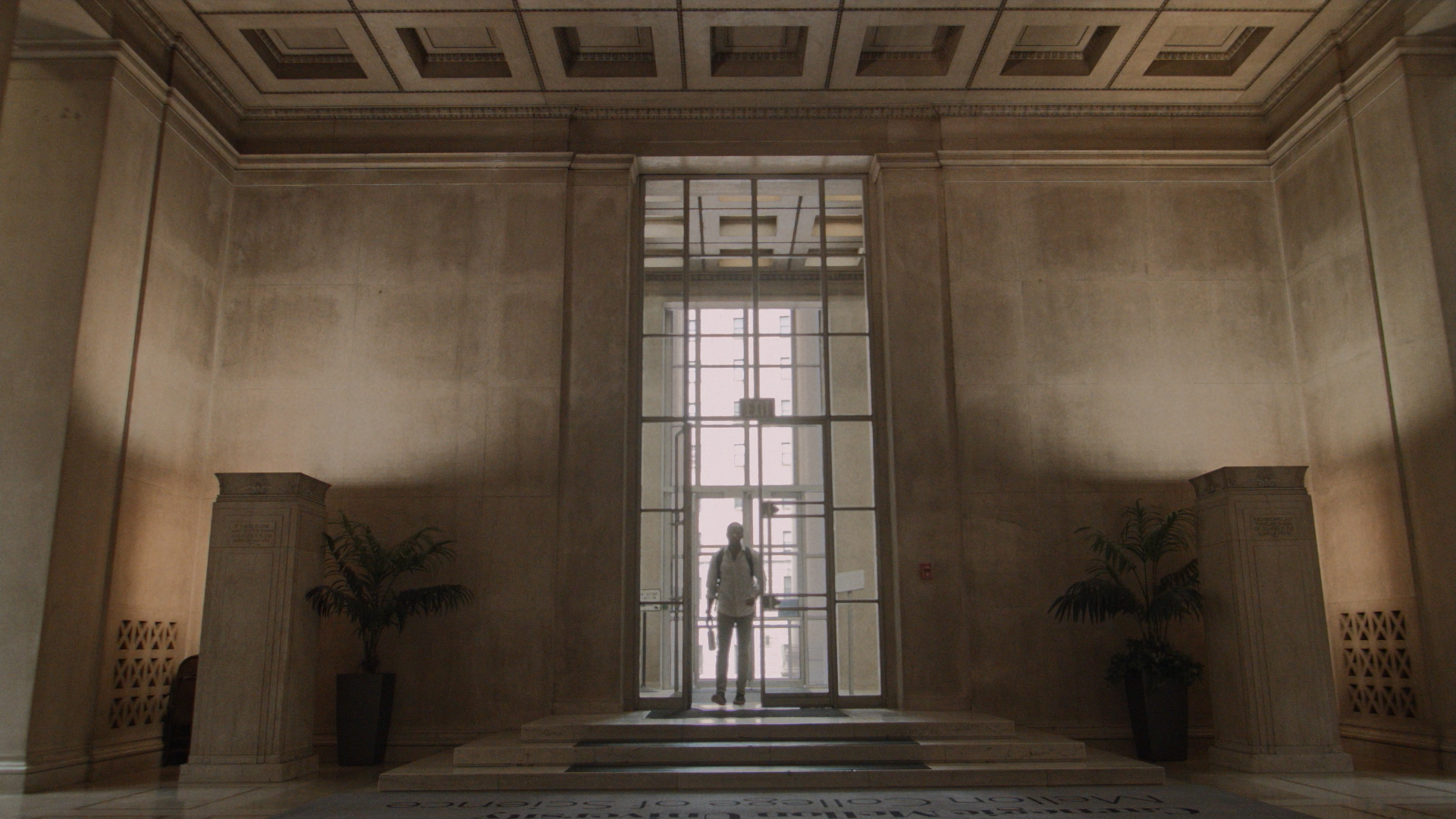 "SEYMOUR (Motell Foster) enters the lobby of CMU's Mellon Institute in ANYA. Note that this is the inside of the door seen in ""The Dark Knight Rises"" image (above). We opted to leave the ""Mellon College of Science"" carpet in place as an Easter egg and thank you to CMU. Still from ANYA by Jacob Okada."