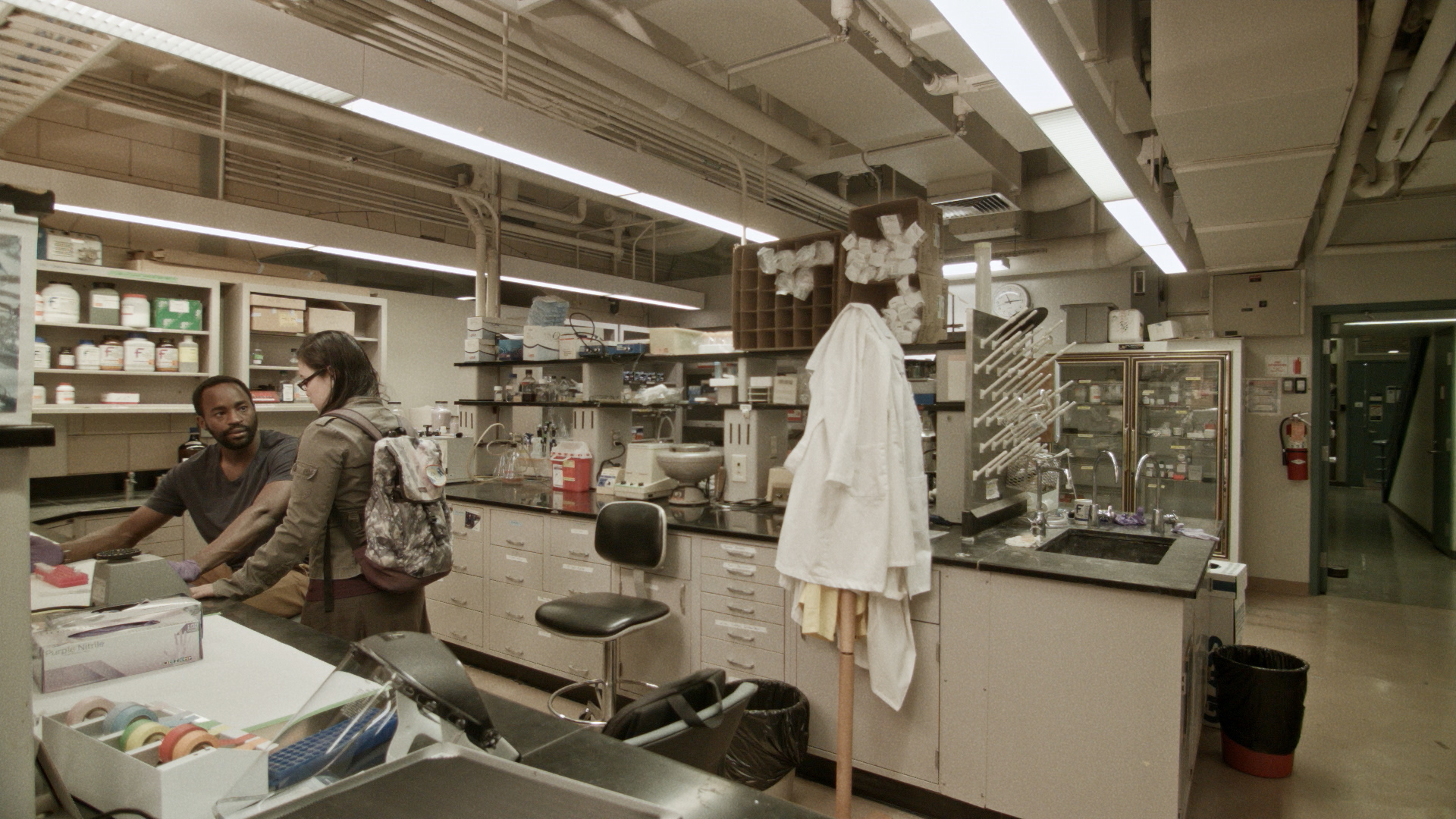 Still from ANYA with DR. SEYMOUR LIVINGSTON (Motell Foster) and RIKA ENDO (Olivia Oguma) in Dr. Andreas Phenning's lab. Still from ANYA by Jacob Okada.