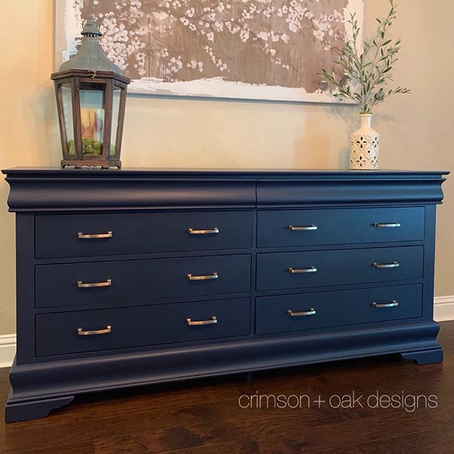 "Finally sharing the full reveal photos of this buffet/sideboard I custom painted for a client over the summer. This navy blue beauty started out as a bedroom dresser but now, after a sleek paint job and gorgeous new transitional drawer pulls, fits right in as the focal point of the eat-in kitchen. 💙  Paint color: @generalfinishes ""Coastal Blue""  Hardware: @schaub_and_company ""Menlo Park Arched Pull"" via @rickshardwareplumbing"
